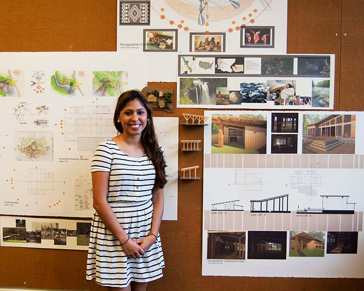 student stands in front of work on display