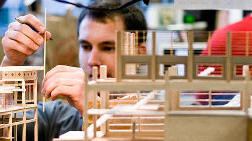 architecture student builds model with wood