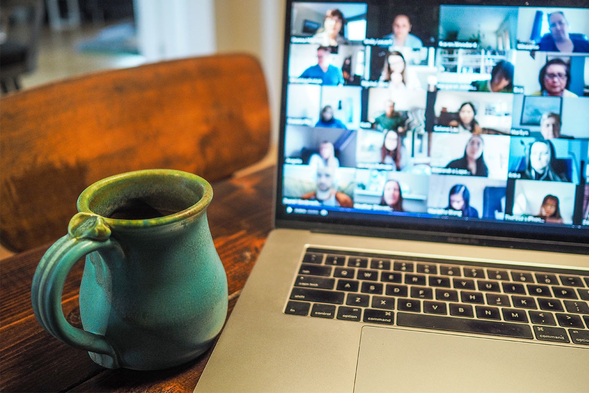 Photo of a mug and laptop with a video chat