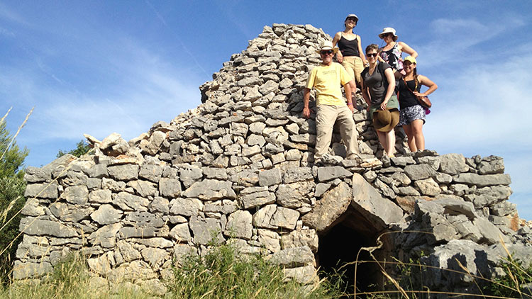 Croatia Field School students stand on stone structure