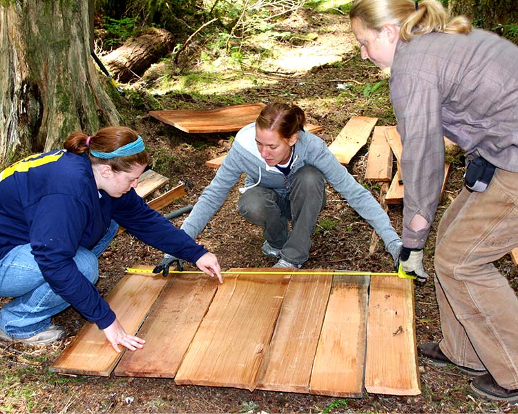 three students measure wood at field school