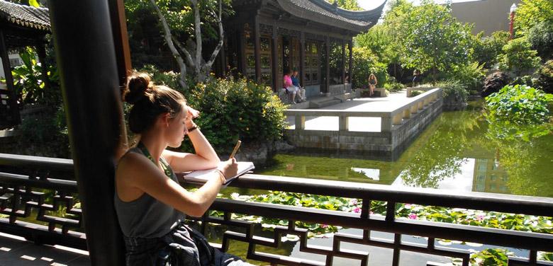 student studies next to pond in garden
