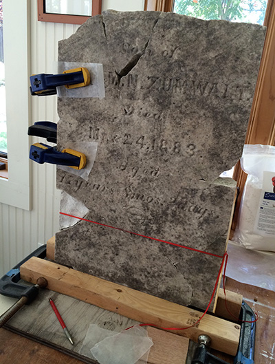 carefully placed clamps stabilize broken pieces of a gravestone