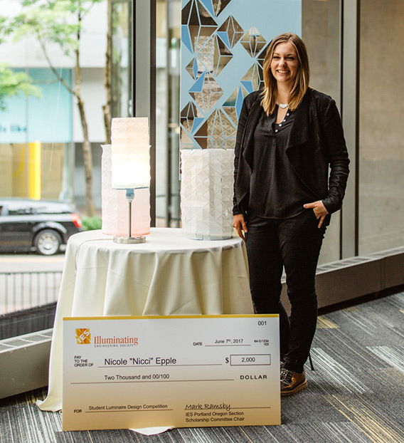 Nicole Epple with lamps and Illuminating Engineering Society of Oregon scholarship check