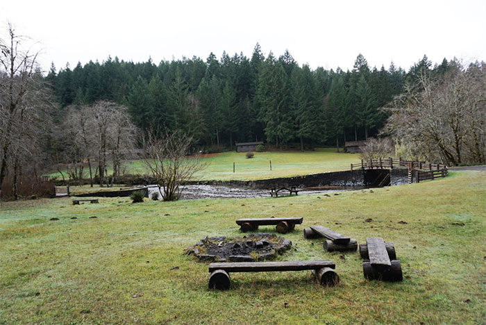 grassy area with fire circle and benches at Silver Falls Youth Camp