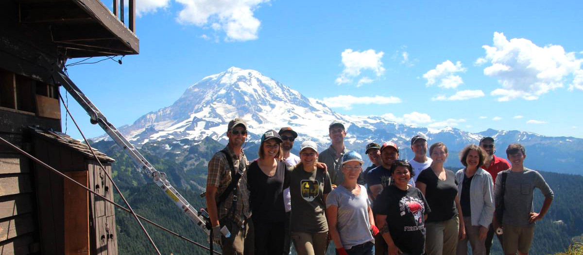 students stand next to fire lookout with Mt. Rainier in background