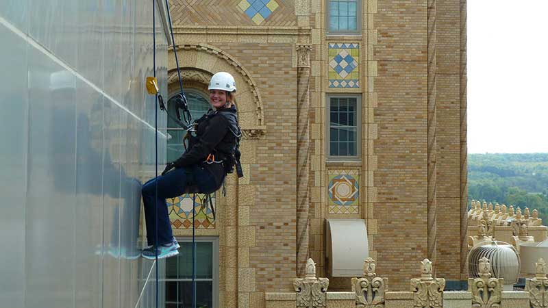 Chelsea Karrels rappels off a Mayo Clinic building while completing a condition assessment of the metal panel and glass tower