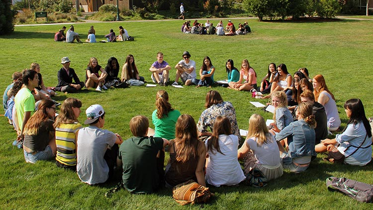 students sit in circles on lawn
