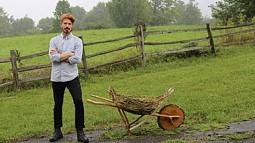 man with a wooden wheelbarrow in a field