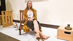 Student Stella May Christ sitting in a wooden chair
