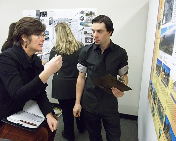 Susan Dolan speaks with student during reviews
